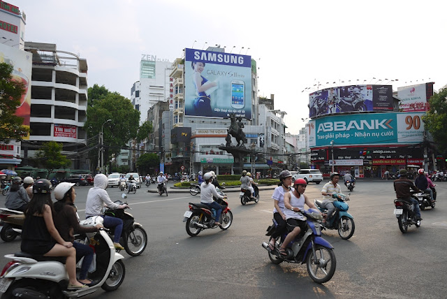 motorbikes crisscrossing each other at a busy intersection in Ho Chi Minh City