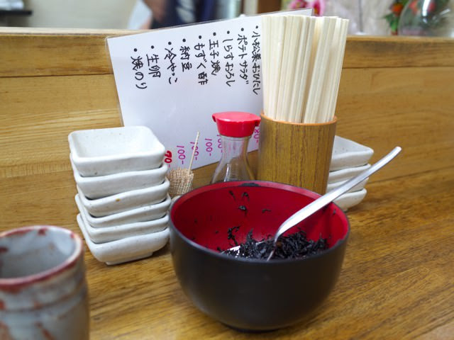 店内のカウンター席の上。箸と小皿と食べ放題の「ひじき」が置かれてる