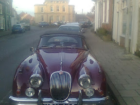 front view of old burgundy sports car with chrome lights & grill