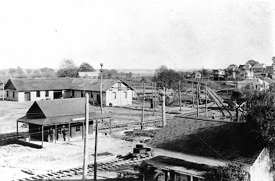 1815 - The L-shaped  Petaluma & Santa Rosa Railway Powerhouse in background, built 1903 from Stony Point Quarry rock.  The Powerhouse served as the freight depot and housed the step-down transformers for the Sebastopol substation for the P&SR electric railway.   In the left foregound is the original wooden Sebastopol depot station.  The Powerhouse was later named the Hogan Building.    Photo facing south easterly, with north and westerly facades visible.  The train tracks seen in the easterly direction comprise the  present day Joe Rodota Trail.