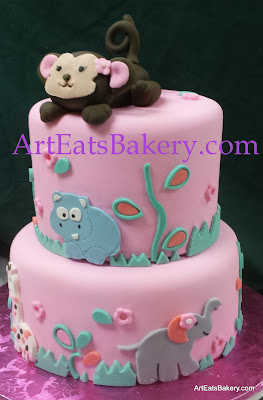 Two tier pink fondant modern creative girl's baby shower cake with edible flowers, hippo, giraffe, elephant, lion and hand made monkey topper