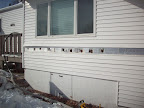 Holes Drilled into a course of siding awaiting insulation