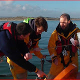Lifeboat Training Coordinator Paul Taylor going through the tool compartment with new trainees Rob and Dave Photo (from video): RNLI/Anne Millman