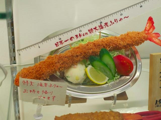 店頭のサンプルケースの定規と並べられた特大海老フライ