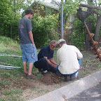 Three generations work on a stubborn post. Uncle, nephew and great nephew.