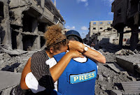 A member of the foreign media, left, cries as she embraces her Palestinian news assistant, right, who burst into tears after discovering his family house was destroyed by Israeli strikes in Beit Hanoun, northern Gaza Strip, Saturday, July 26, 2014. Thousands of Gaza residents who had fled Israel-Hamas fighting streamed back to devastated border areas during a lull Saturday, and were met by large-scale destruction: scores of homes were pulverized, wreckage blocked roads and power cables dangled in the streets. (AP Photo/Lefteris Pitarakis)