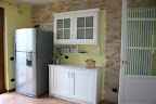Realizzazione cucina country, particolare credenza e muro rivestito in pietro in contrasto col frigorifero moderno