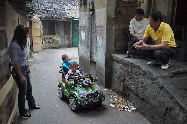 adults watching two boys, one in an electric toy car, in a small alley near Beizheng Street in Changsha
