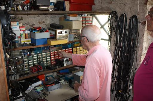 Achter zijn werktafel heeft hij zijn grijpvoorraad kleine componenten.