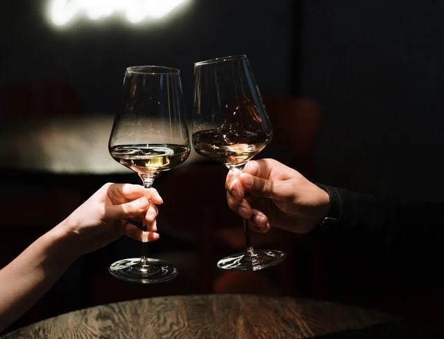 Toasting wine glass during anniversary date at home