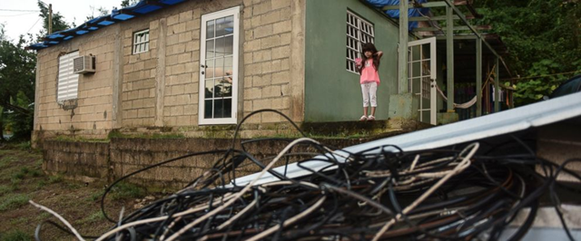 In this 22 December 2017 photo, six year old Melanie Oliveras González stand on the porch of her house, in front of a handful of electric cables knocked down by the winds of Hurricane Maria, in Morovis, Puerto Rico. Morovis has been without power since hurricane smashed into the island in November. Photo: Carlos Giusti / AP Photo