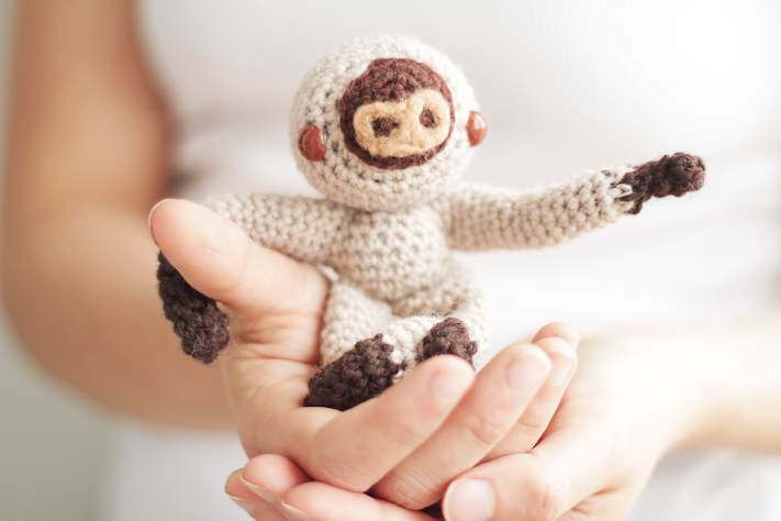 Amigurumi sloth sitting in the hands.