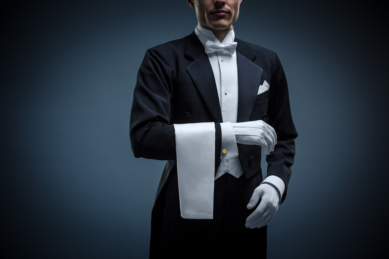 Waiter in a tuxedo on a black background