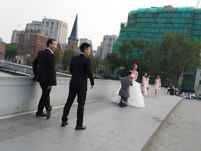 posing for wedding photos on a bridge in Shanghai