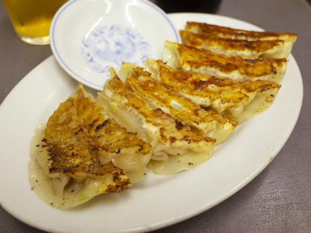 楕円皿に盛られた餃子8個。脇には酢醤油用の小皿が差してある。