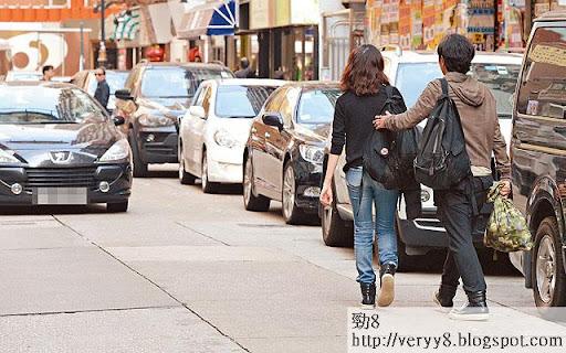 有車經過,伊健立即伸手扶一扶老婆。