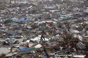 A man stands atop debris and ruins of houses