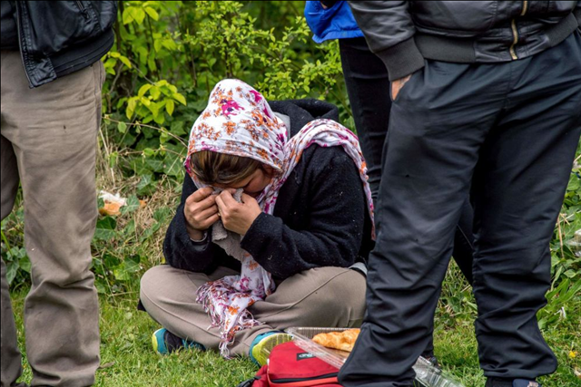 A woman reacts while migrants wait to board buses in Grande-Synthe, northern France, on 14 April 2017, as they leave a makeshift camp where around 300 migrants had found shelter after the destruction by a fire of their nearby camp, to head to reception and orientation centres. A huge fire gutted one of France's biggest migrant camps housing 1,500 people, which started after a brawl involving hundreds of Afghans and Kurds late on 10 April 2017. The Grande-Synthe facility near the northern French port of Dunkirk was the only one in the area and provided hundreds of wooden huts for shelter, as well as cooking facilities and showers. Photo: PHILIPPE HUGUEN / AFP / Getty Images