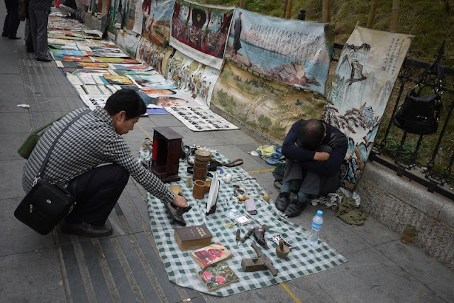 a man sleeping next to his items for sale outside Tianxinge Antique City in Changsha, China