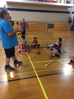Dr. John McMahon explaining goal ball to athletes in the gym