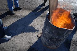 Burning barrels of scrap wood keep fingers warm on a cold January day in Willets Point.