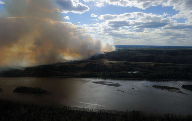 Aerial view of smoke rising near highway 63 south of Fort McMurray, taken from a CH-146 Griffon helicopter on 5 May 2016. Photo: MCpl VanPutten / Department of National Defence in Canada / Anadolu Agency / Getty Images