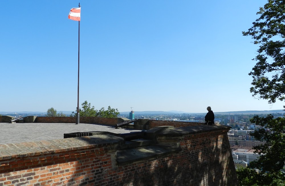 a young monk in contemplation as he looks over the city, beside the ancient city walls.... the yellow and white Brno city flag flies at the castle; looks just like the Austrian flag without the eagle!
