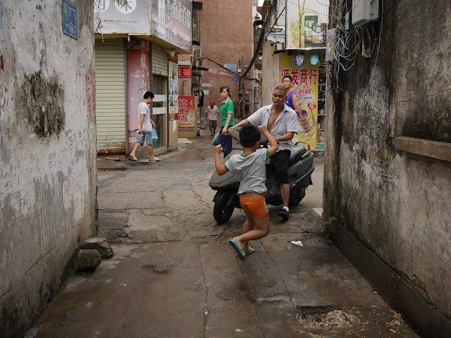 boy jumping out of the way of a man riding a scooter