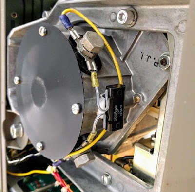The head positioning motor moves the heads back and forth. Drive wires (yellow) are bolted to the motor. A bypass capacitor (black) is connected across the motor.