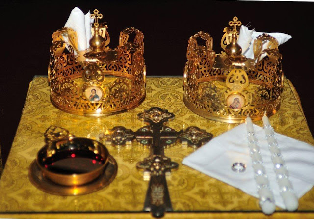 The table is prepared with the bridal crowns (symbolizing the heavenly crowns we strive for through marriage) the common cup of wine, the hand-cross, and two candles held by the couple.