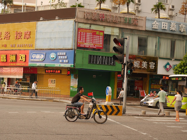 young man riding an electric bicycle with a PRC flag in Zhongshan, China