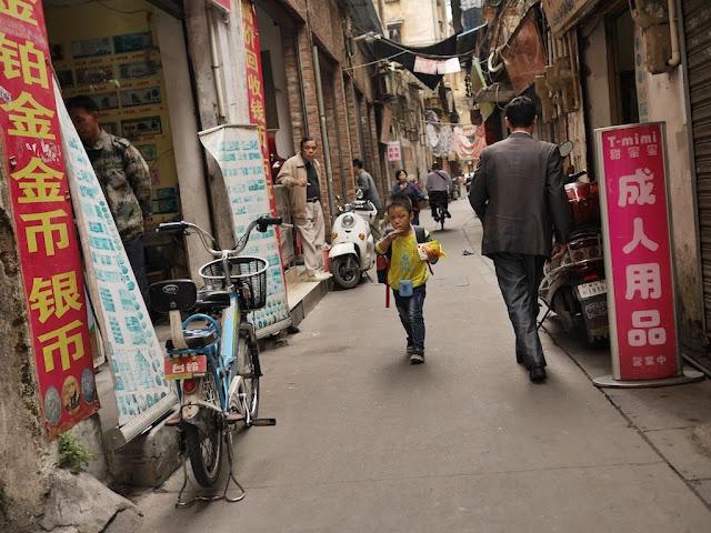 boy eating while he walks down Wuya Lane in Shaoguan, Guangdong