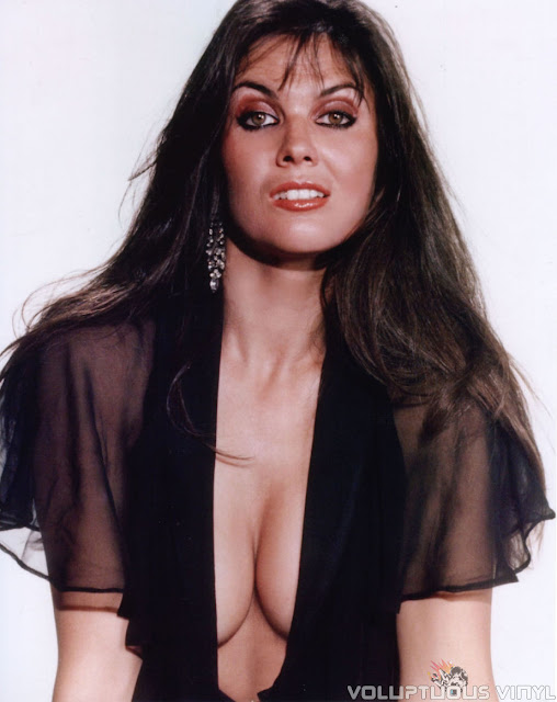 Caroline Munro black sheer top showing deep cleavage.