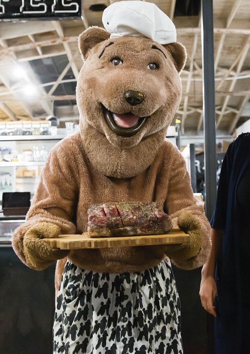 photo of Bear holding a platter of steak