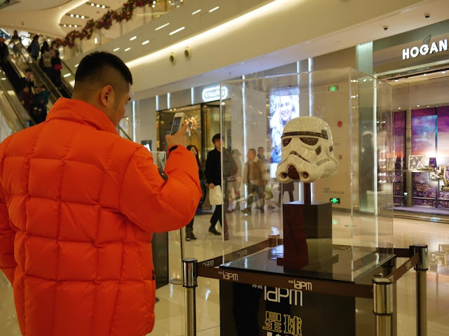 man taking a photograph of a Star Wars Stormtrooper head at the IAPM shopping center in Shanghai
