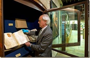 Samuel Rubio, canónigo de la Catedral de León, manipula el códice en la vitrina del museo.