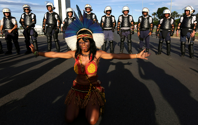 A Pataxo indigenous woman performs in front of police during the Indigenous Peoples Ritual March outside the National Congress in Brasilia, Brazil, Thursday, 27 April 2017. Photo: Eraldo Peres / AP Photo