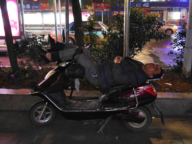 man sleeping on a motorbike with his legs propped up on the handlebars