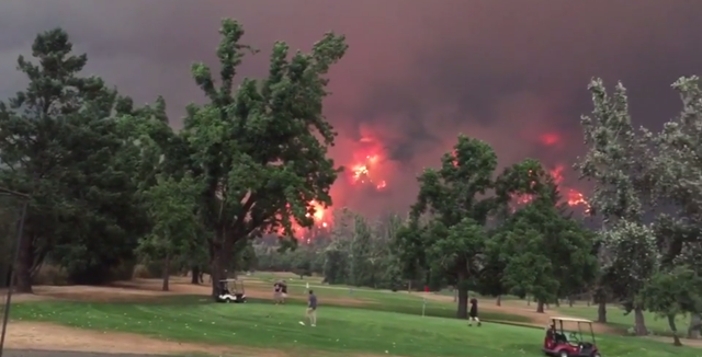 People play golf as the Eagle Creek Fire burns on both sides of the Columbia River Gorge in Washington and Oregon, 4 September 2017. Photo: Hal Bernton / The Seattle Times