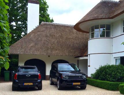 Dwa samochody stojące przed elegancką willą z dachem krytym trzciną