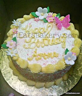 White and yellow custom buttercream women's birthday cake with sugar flowers and butterfly