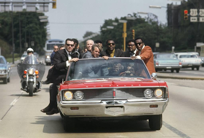 photo of Bobby Kennedy in red car as he campaigns in Indiana during May of 1968, with various aides and friends: former prizefighter Tony Zale and (right of Kennedy) N.F.L. stars Lamar Lundy, Rosey Grier, and Deacon Jones by Bill Eppridge