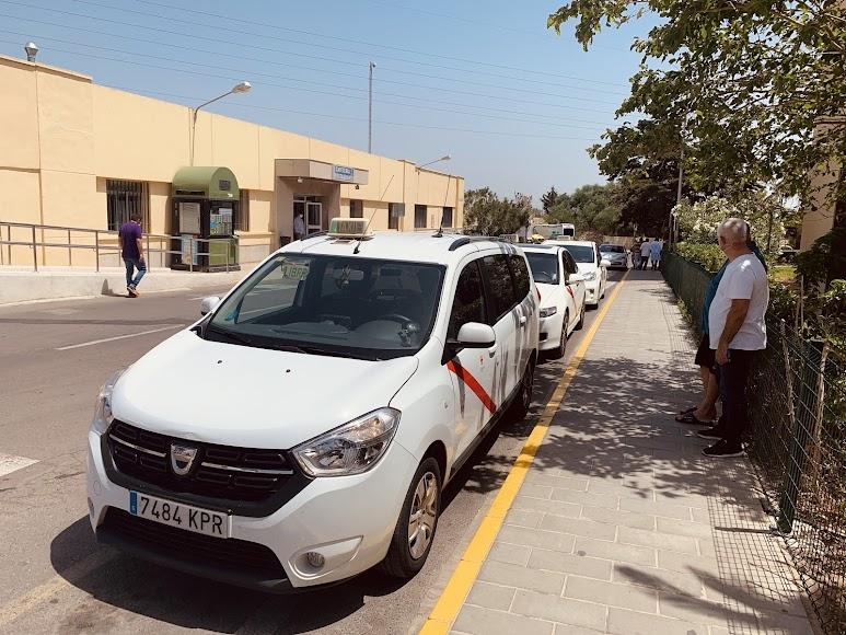 Dos taxistas se resguardan en la sombra de un árbol en la parada del Hospital Torrecárdenas.