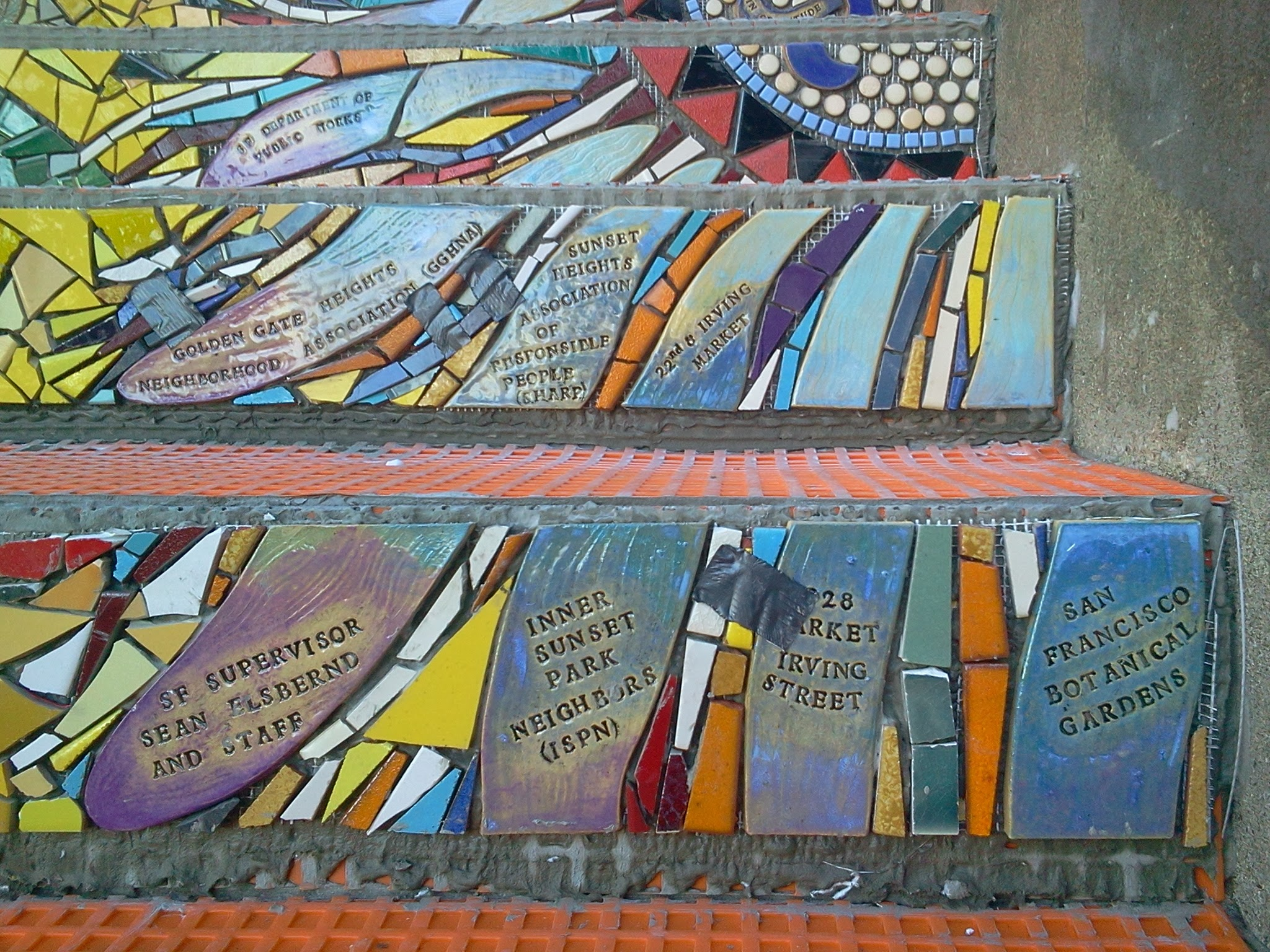 """Photo: Detail of bottom half of passion flower (the """"Gratitude"""" element, thanking organizations and businesses that provided substantial support and in-kind gifts) on the fourth flight of steps (from bottom) of the Hidden Garden Steps (16th Avenue, between Kirkham and Lawton streets in San Francisco's Inner Sunset District) installed on October 31, 2013. KZ Tile workers finished installing more than 80 pieces of the 148-step ceramic-tile mosaic designed and created by project artists Aileen Barr and Colette Crutcher. For more information about this volunteer-driven community-based project supported by the San Francisco Parks Alliance, the San Francisco Department of Public Works Street Parks Program, and hundreds of individual donors, please visit our website at http://hiddengardensteps.org."""