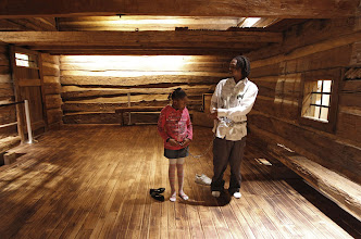 Photo: Robert Cooley teaches daughter Cree Rayford, 7, the history of the slave house and why chains were used, as they tour the National Underground Railroad Freedom Center in Cincinnati, Ohio. Photo by Jeff Swinger, The Cincinnati Enquirer.