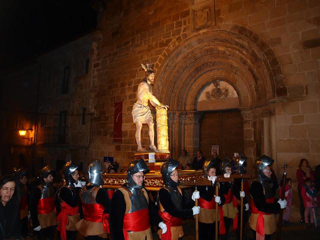 La procesión que conduce el paso de Cristo atado a la Columna, frente a la fachada de la iglesia de Santiago