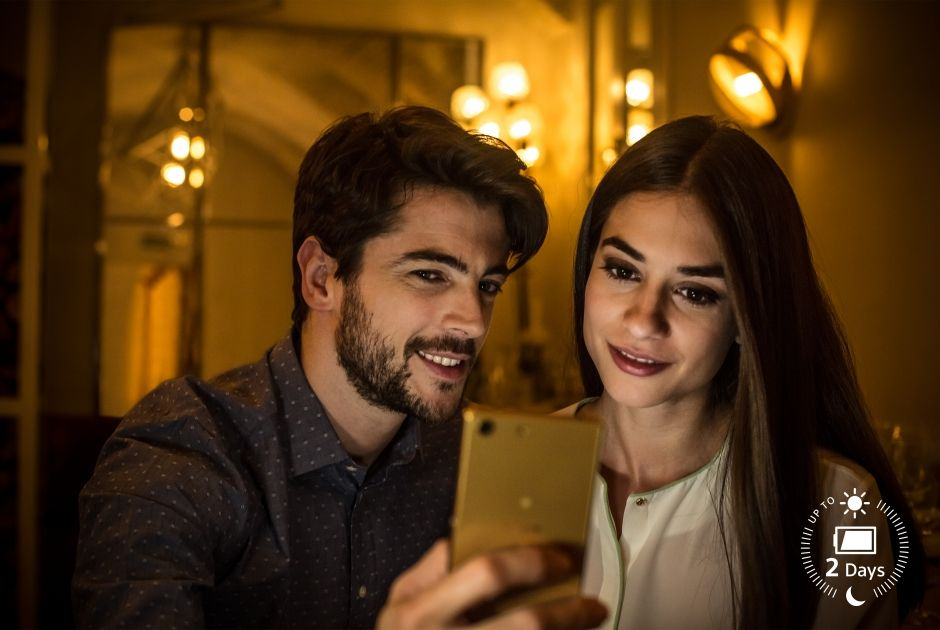 Two people looking at their phone in a restaurant at night