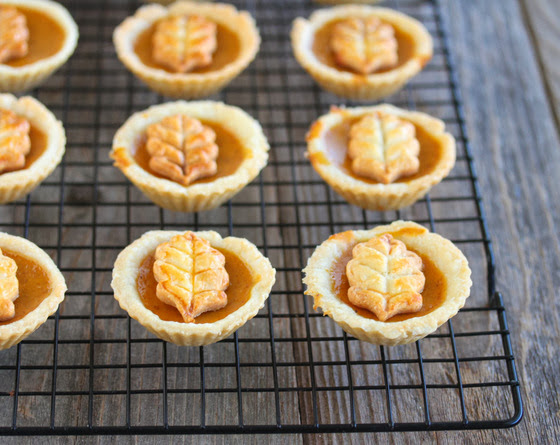 close-up photo of mini pumpkin pies lined up on a baking sheet