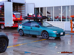 Mazda 323F / Lantis with go cart on roof