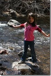 Little girl on rock in stream